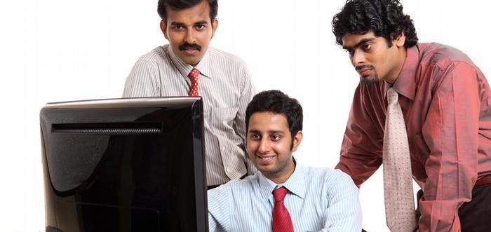 外国人エンジニア3人がパソコンに向かって笑っている画像
