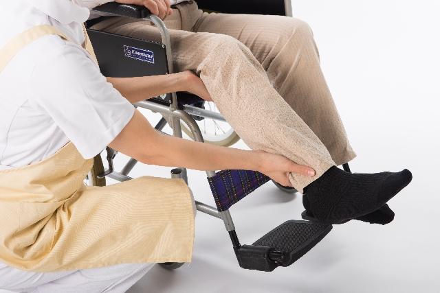 車椅子に座る老人の男性を介護する女性介護士の画像