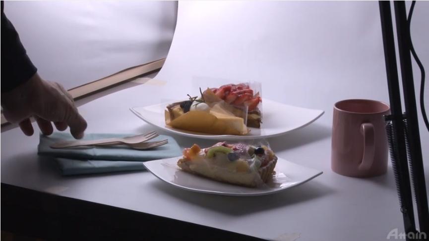 オンライン商品写真講座の動画のワンカット画像。ケーキをおいしそうに見せる写真の撮り方について解説している様子